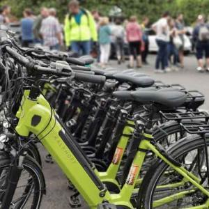 E-Bikes in Reihe mit Teilnehmer im Hintergrund