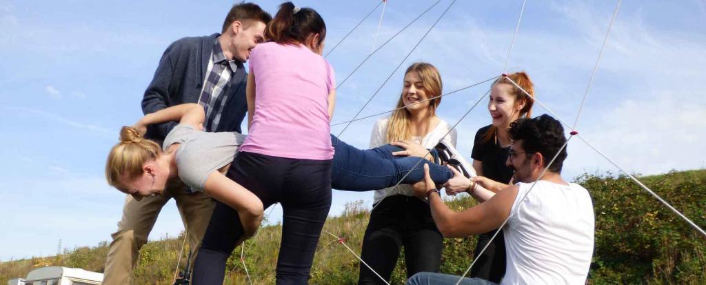 Fünf Personen tragen Kollegin durch eine Teamevent Aufgabe