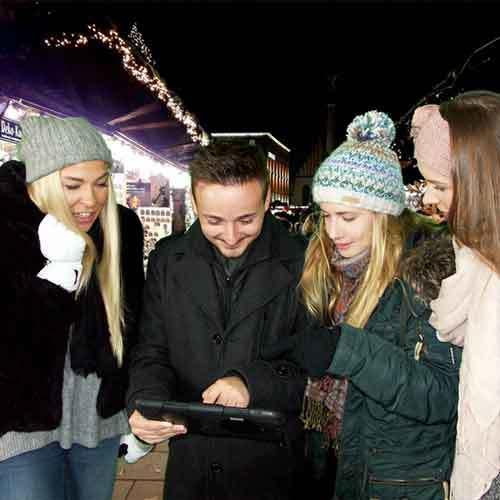 Gruppe am Tablet auf Weihnachtsmarkt