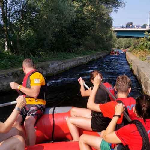 Team im Raft auf Bootsrutsche