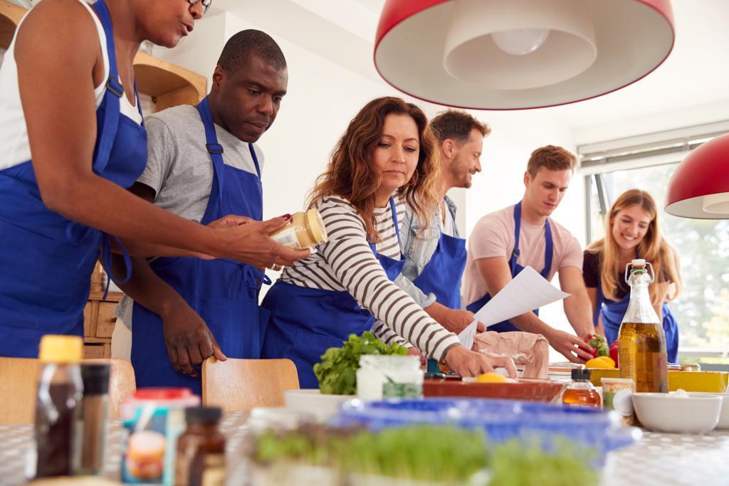 sechs Personen beim kochen